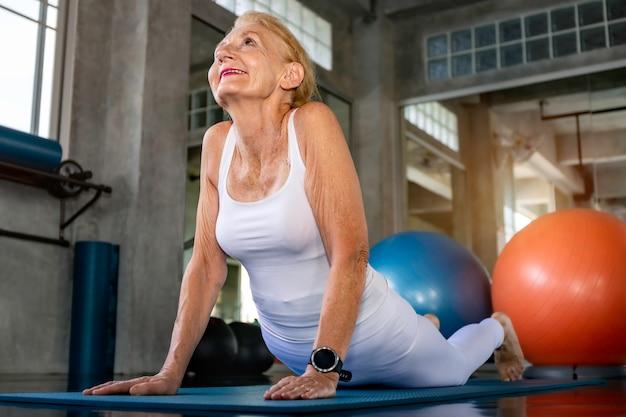 Caucasiano mulher sênior fazendo exercícios de ioga no ginásio.