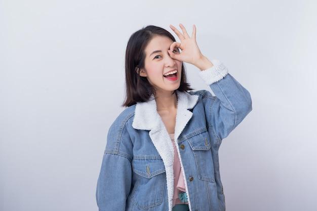 Caucasiano, mulher sorridente, mostrando, dela, mão, com, ok, sinal, positivo, feliz, jovem, menina asiática, desgastar, azul, roupa casual, retrato