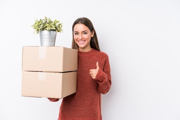 Caucasic jovem segurando caixas sorrindo e levantando o polegar