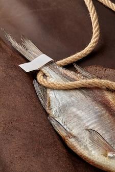 Cauda de barata seca com etiqueta de papel e corda grossa em fundo de couro marrom