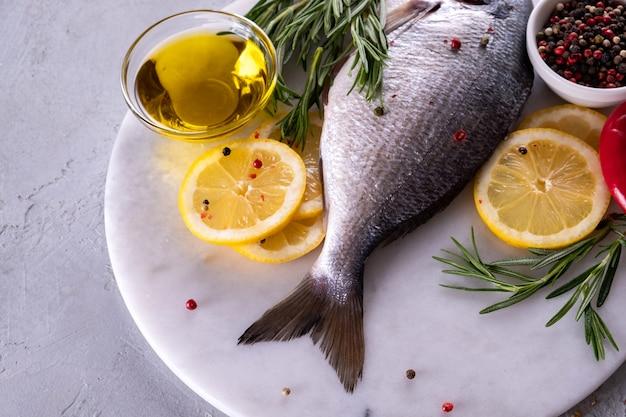 Cauda de peixe cru fresco dorado ou sargo na placa de mármore com especiarias, ervas, limão e sal. vista do topo