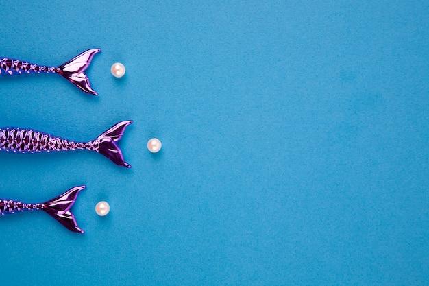 Caudas brilhantes de sereias em um fundo azul