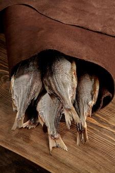 Caudas de baratas secas em um pacote de couro com fundo de madeira