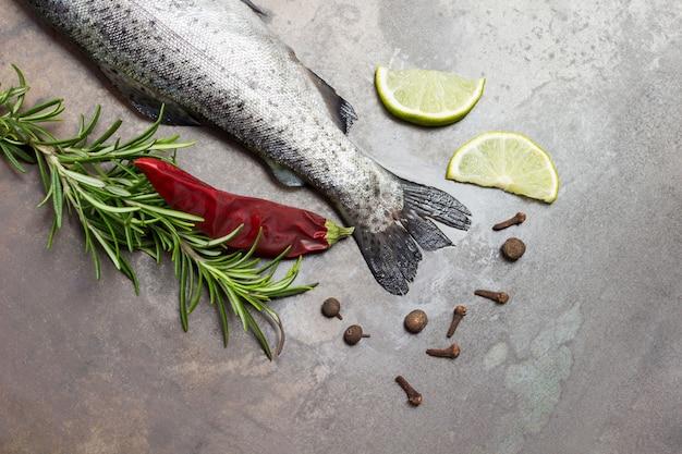 Caudas de peixe truta crua com raminhos de alecrim, rodelas de limão e pimenta. copie o espaço. fundo enferrujado metálico. postura plana
