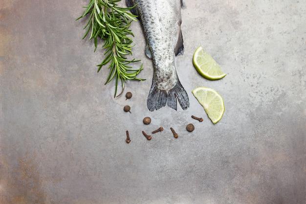 Caudas de peixe truta crua com raminhos de alecrim, rodelas de limão e pimenta.