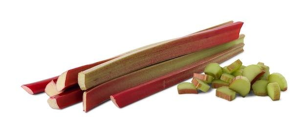 Caules grossos e avermelhados de ruibarbo (rheum rhaponticum) sem folhas e pedaços cortados isolados no fundo branco.