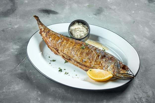 Cavala assada apetitosa e saudável com tártaro de vegetais e limão, servida em um prato branco sobre uma superfície cinza