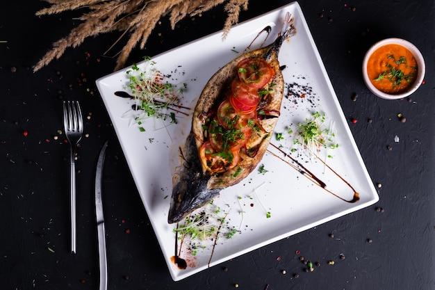 Cavala assada com legumes em um prato, em uma superfície escura
