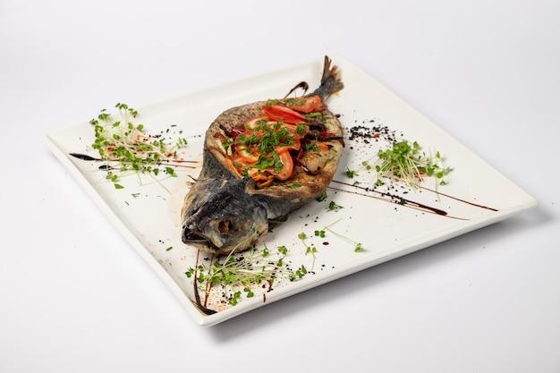 Cavala assada com legumes em um prato, sobre uma superfície branca