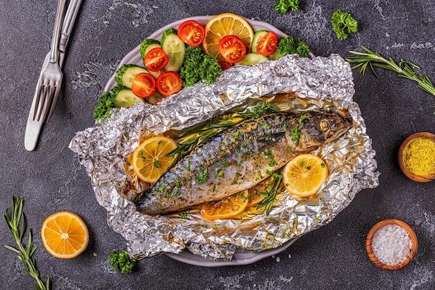 Cavala assada em papel alumínio com legumes em um prato, vista de cima