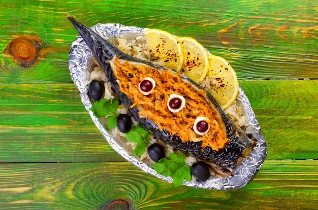 Cavala assada peixe recheado com cenouras, azeitonas, salsa encontra-se em um prato embrulhado em papel alumínio. Foto Premium