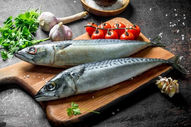 Cavala de peixe cru fresco em uma placa de corte com tomate, ervas e dentes de alho. na mesa rústica escura