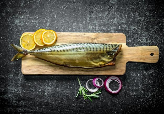 Cavala de peixe defumado em uma tábua de madeira com anéis de cebola e rodelas de limão. em rústico escuro