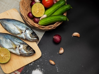 Cavala fresca e ingredientes para cozinhar. Especiarias e legumes na mesa preta