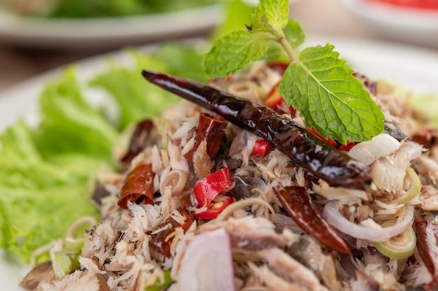 Cavala frita coberta com galanga, pimenta, hortelã, cebola vermelha em um prato branco.