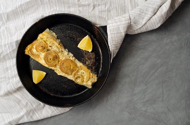 Cavala trachurus assada frita com cebola e ervas secas em uma frigideira velha em uma toalha