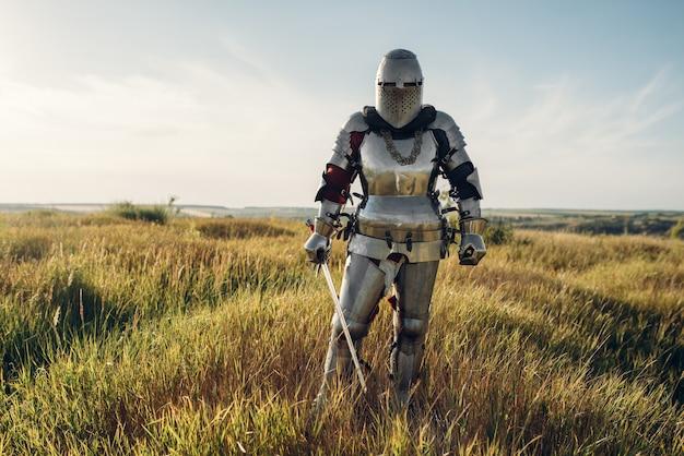 Cavaleiro de armadura e capacete segura a espada. antigo guerreiro com armadura posando no campo