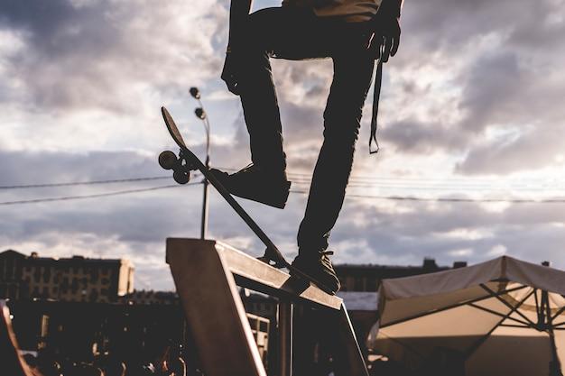 Cavaleiro de pé em um skate antes do truque contra o céu