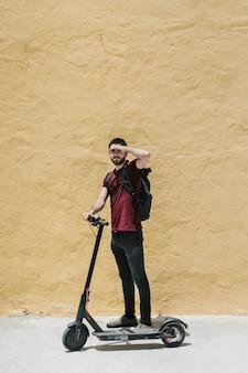Cavaleiro de scooter cobrindo os olhos