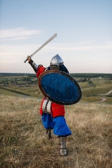 Cavaleiro medieval com poses de espada na armadura, lutador