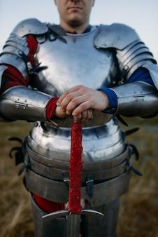 Cavaleiro medieval em armadura de metal segura a espada, grande batalha. antigo guerreiro com armadura posando no campo