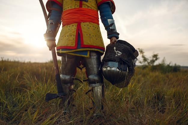 Cavaleiro medieval em armadura segura machado e capacete, grande torneio. antigos guerreiros com armaduras posando no campo