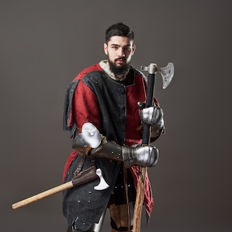 Cavaleiro medieval em cinza. retrato de guerreiro brutal rosto sujo com armadura de cota de malha vermelha e preta roupas e machado de batalha
