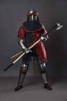 Cavaleiro medieval em fundo cinza. retrato de guerreiro brutal de rosto sujo com roupa vermelha e preta de armadura de cota de malha e machado de batalha.