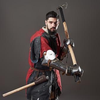 Cavaleiro medieval em fundo cinza. retrato de guerreiro de rosto brutal com roupa vermelha e preta de armadura de cota de malha e machado de batalha.