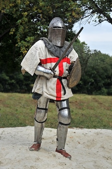 Cavaleiro medieval em sua armadura com escudo e espada