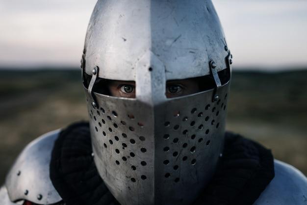 Cavaleiro medieval na visão do close up da armadura e do capacete, grande batalha. antigo guerreiro com armadura posando no campo