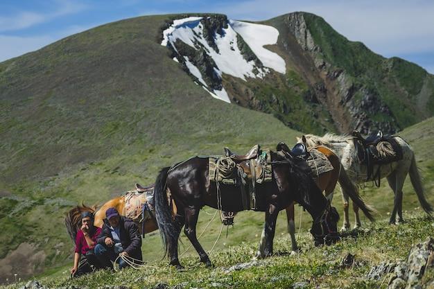 Cavaleiros jovens e velhos caminham com três cavalos na encosta da montanha no distrito de ulagansky da república de altai, rússia