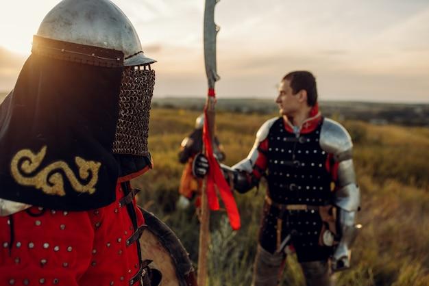 Cavaleiros medievais em armadura e capacete ao pôr do sol, grande torneio. antigo guerreiro com armadura posando no campo