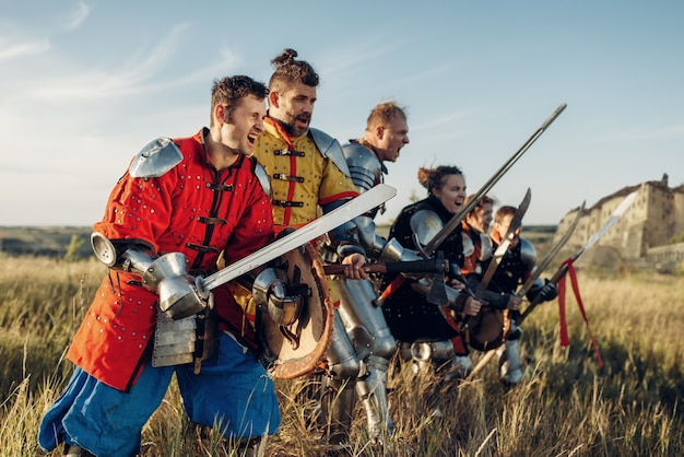 Cavaleiros medievais em armaduras e capacetes em uma fileira antes da batalha. antigo guerreiro com armadura posando no campo