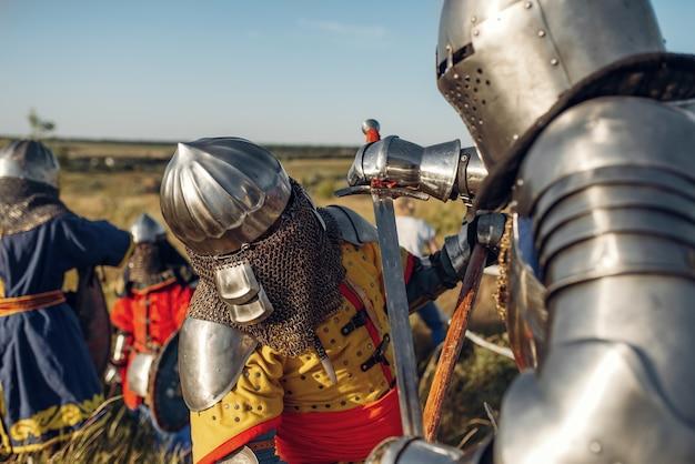 Cavaleiros medievais em armaduras e capacetes lutam com espada e machado. antigo guerreiro com armadura posando no campo