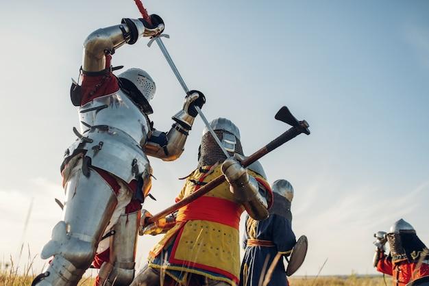 Cavaleiros medievais em armaduras e capacetes lutam com espada e machado, grande batalha. antigo guerreiro com armadura posando no campo