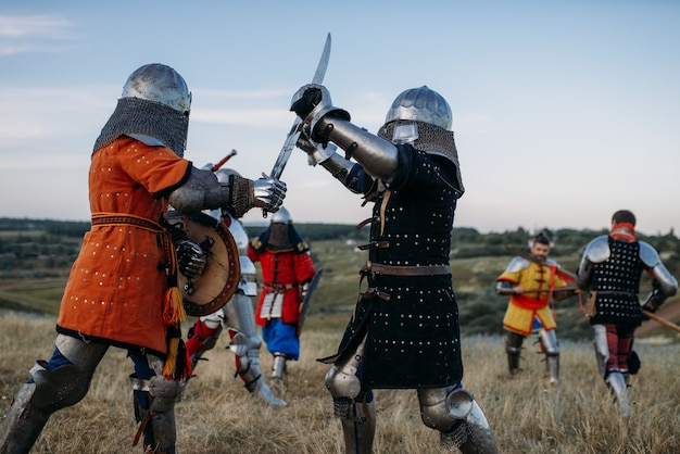 Cavaleiros medievais em armaduras e capacetes lutam com espadas. antigos guerreiros armados posando no prado