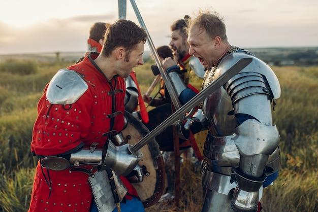 Cavaleiros medievais lutam com espada e machado
