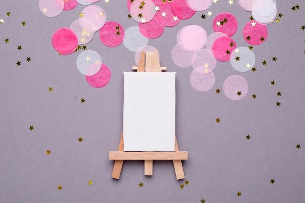 Cavalete de desenho e confete rosa em cinza