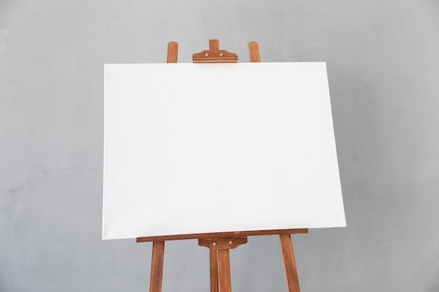 Cavalete de madeira com tela branca em branco em estúdio. copie o espaço para o seu texto