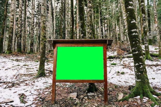 Cavalete de madeira estacionário vazio na floresta entre as árvores