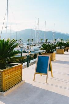Cavalete de madeira fica na marina contra iates brancos estacionados