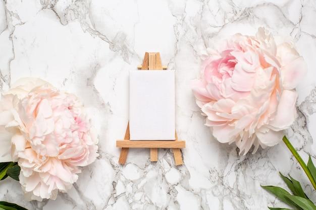 Cavalete pequeno para pintura com lona e flores de peônia rosa na superfície de mármore.
