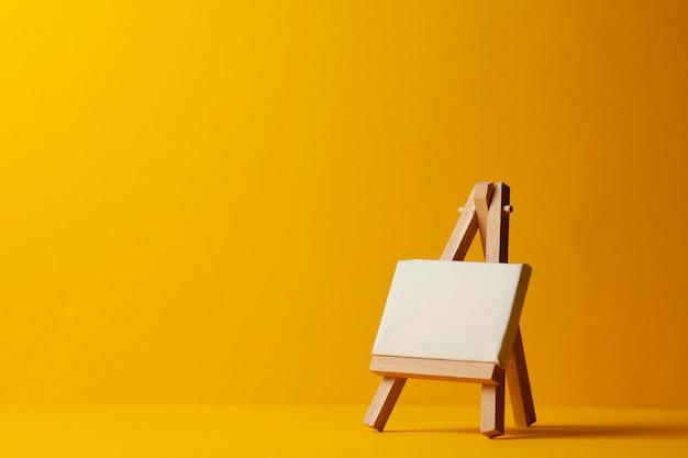Cavalete vazio pequeno para desenhar em um fundo amarelo, conceito de arte, desenhando