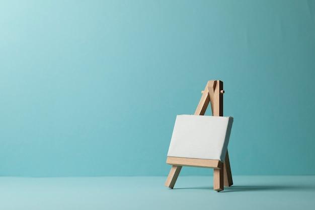 Cavalete vazio pequeno para desenhar sobre um fundo azul