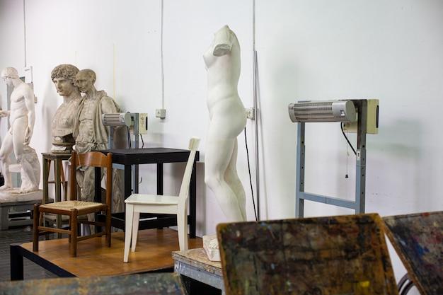 Cavaletes, estátuas e cadeiras na sala de pintura da escola de belas artes