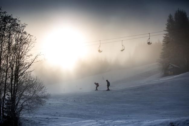 Cavalgando esquiadores e teleférico contra o forte sol de inverno