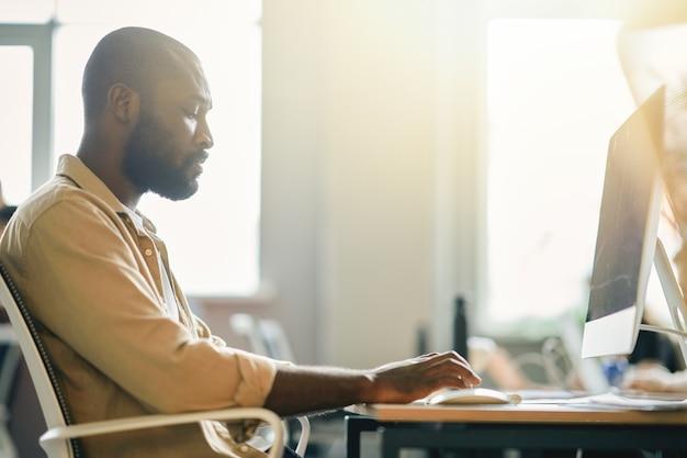 Cavalheiro afro-americano sério trabalhando em um computador