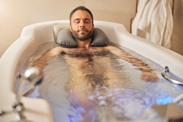 Cavalheiro barbudo relaxando na banheira durante procedimento de hidroterapia
