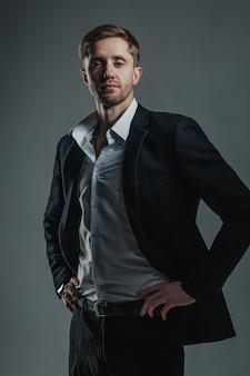 Cavalheiro bonito posando em um terno escuro e camisa branca.